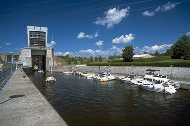 Boats leaving the lock and others on the dock awaiting next lockage upstream. To the right, Carillon park.