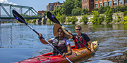 Two kayakers are paddling on the Lachine Canal during the summer