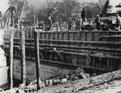 Thirteen workmen on the wood formwork that restrains concrete, during the construction of the present lock in the Saint-Ours canal in 1931.