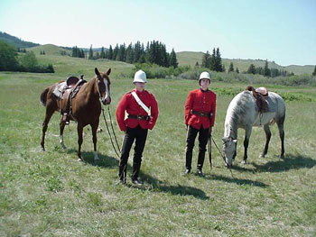 Two Parks Canada staff dressed in period NWMP uniform standing with their horses.