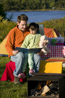 Man and child reading in their campsite