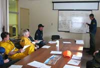 Incident Commander briefs staff sitting around a table