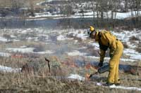 park warden burning grass amid snow, river in background