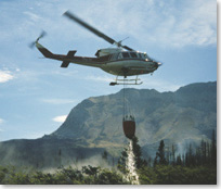 Picture of a helicopter dropping water over the Sofa Mountain fire