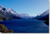 A view of Upper Waterton Lake, a long stretch of sparkling waters surrounded by mountains