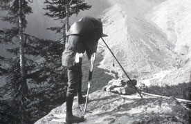 black and white photo of man photographing glacier