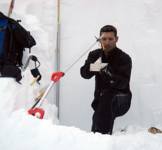 Ali Haeri determines snow density using a modern weighing scale, 2012