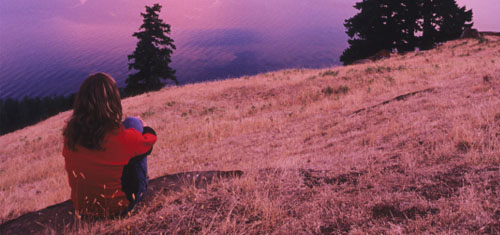 A woman perched on the Mt. Warburton Pike during sunset