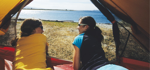 Kids in a tent along the shoreline