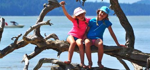 Two girls sit on the branches of a tree in Gulf Islands National Park Reserve