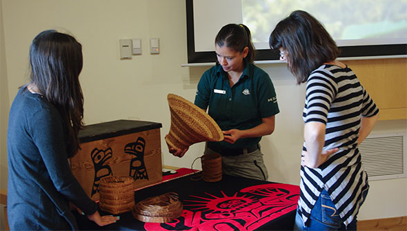 A Parks Canada interpreter shows visitors examples of how cedar is used by the Haida