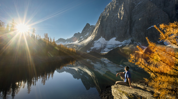 A hiker sits next to Floe Lake