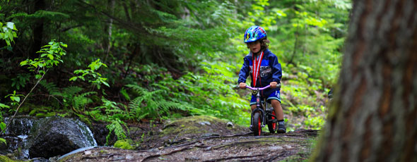 child on bicycle in forest