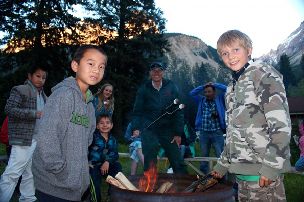 Two boys roast marshmallows at a Learn to Camp program.