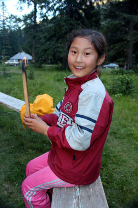 A young girl holds a lit piece of campfire kindling.