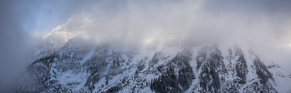Fog envelopes a peak in Kootenay National Park during the winter.