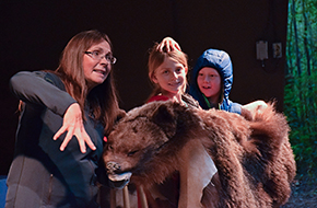 Children learn about bears at a theatre show