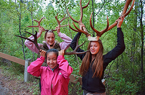 Three girls hold antlers on their heads