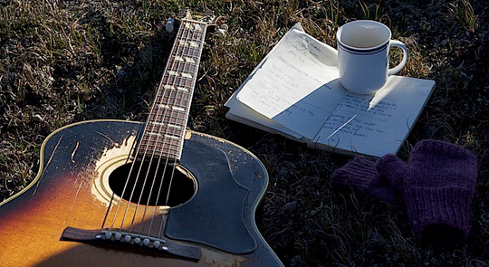 Kathleen's guitar and notebook; as she takes a break from writing a song in the park