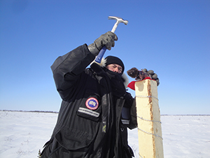 Rodney Redhead, Parks Canada Resource Management Technician, attaching bait to the top of a post for the wolverine project