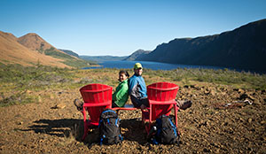 People taking in the view of the Tablelands and Trout River Pond from our red chairs.