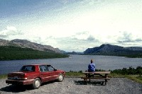 Car and visitor at picnic area with view of Trout River Pond.