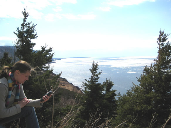 Woman looking at her Global Positioning System unit in Cape Breton National Park