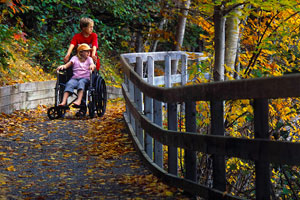 A visitor in a wheelchair is guided along the Freshwater Lake trail