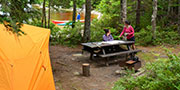Campers enjoying a backcountry campsite with tent and canoe