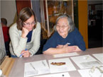 An archaeologist and an Inuvialuit Elder gather at a table to look at an Inuit artifact from the park.
