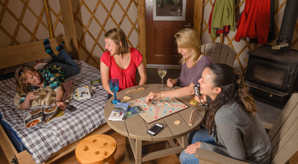 A group plays scrabble in a yurt