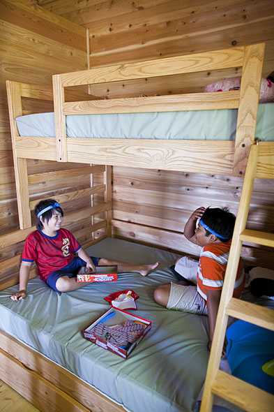 kids play a card game on bunk beds