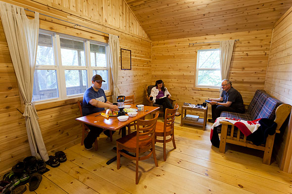 a famly enjoys supper inside a cabin