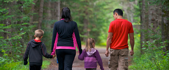 Two grown-ups and two children walking hand in hand along a trail.