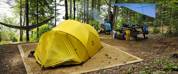 Yellow tent at a canoe-campsite in the foreground with a family in the background.