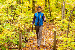 A woman is walking with hiking poles on a trail surrounded by trees with yellow foliage.