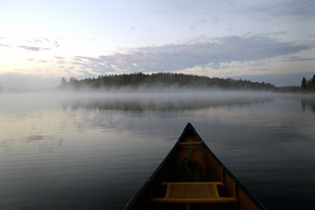 A sunrise in the mist; in the foreground there is a canoe.