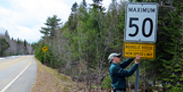 A park employee installs a new speed limit sign.