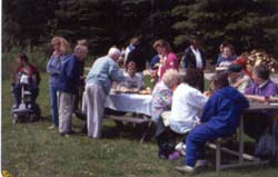 Group of people at picnic table having a meal and visiting.