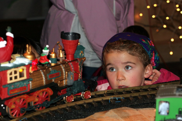 A girl stares in wonder at an electric train