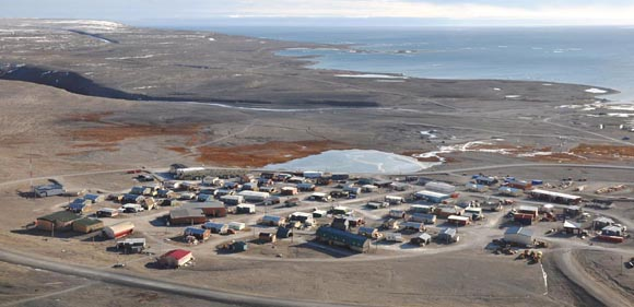 A view from the top of a hill; overlooks a small Arctic village, at the edge of the ocean.