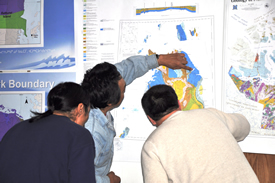 Three people gather around a map to look at its features.