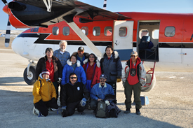A group of people pose on a landing strip by the open door of a twin otter aircraft