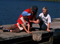 A park naturalist helps young visitors discover life in the lake