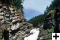 Picture of the small Cameron falls which fall from two different points. Rocks and the sky surround them.