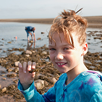 Young girl holding a crab in her hand