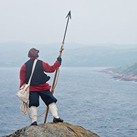 A fisherman watching the sea a harpoon in his hand