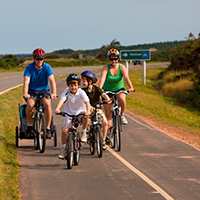 Young family cycling near the sea path