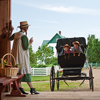 Anne of Green Gables waves to young visitors in a horse bugs