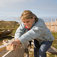 A woman is doing some carpentry under the observation of a viking